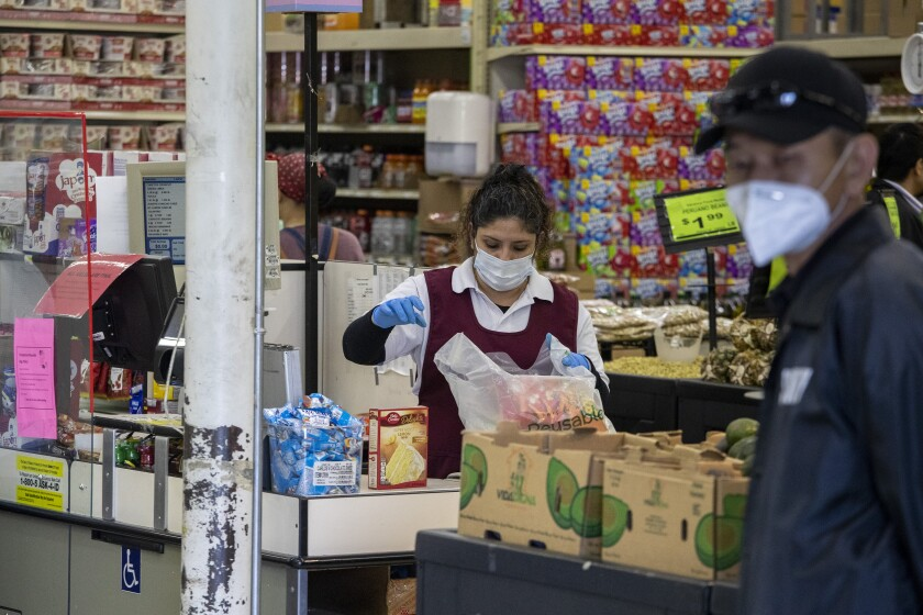 Supermarket cashier wears a masks