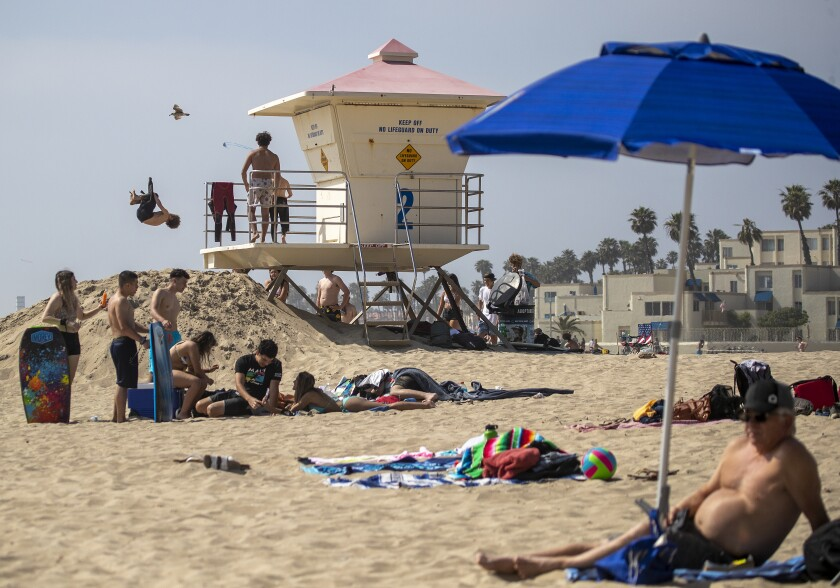 """Children do flips off the lifeguard tower while others relax on the last day of open beaches in Huntington Beach after Gov. Gavin Newsom on Thursday announced the """"hard close"""" of all Orange County beaches."""