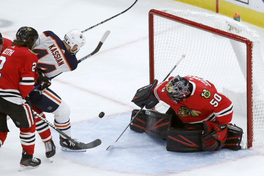 Chicago Blackhawks goaltender Corey Crawford (50) makes a point-blank save on a shot by Edmonton Oilers' Zack Kassian (44) during the third period of an NHL hockey game Monday, Oct. 14, 2019, in Chicago. (AP Photo/Charles Rex Arbogast)