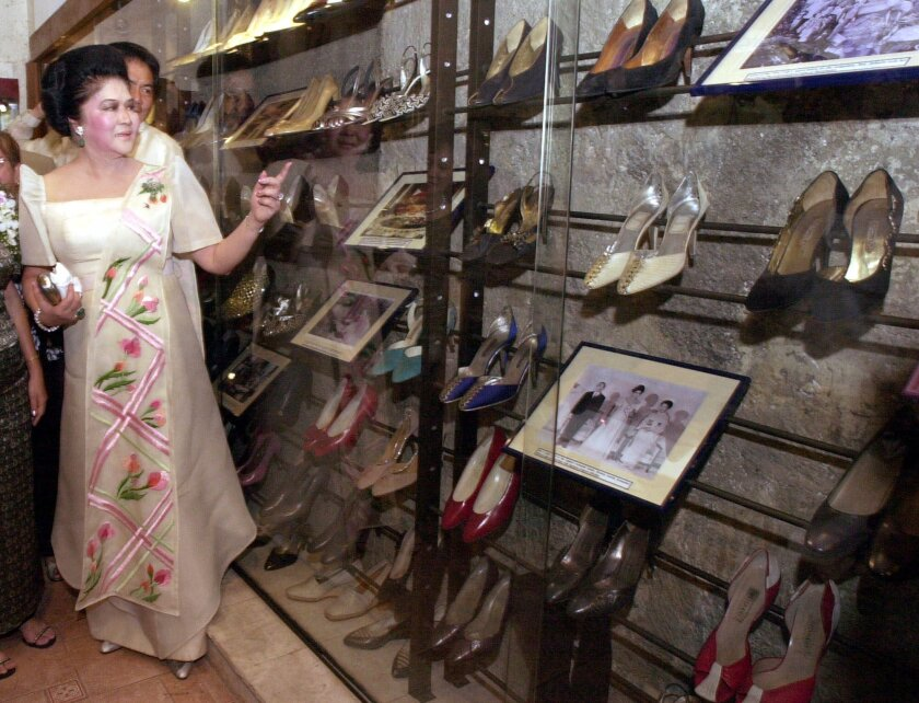 Former First Lady Imelda Marcos points to some of her 200 shoes on display