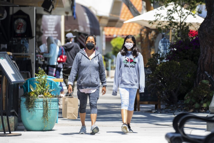 Redondo Beach, CA - May 14: Two masked women walk along S. Catalina Avenue in the Riviera Village shopping area of Redondo Beach, CA, a day after the Centers for Disease Control and Prevention (CDC) loosened guidelines for vaccinated people, with masks no longer being necessary when outdoors or in most indoor situations, Friday, May 14, 2021. The new guidelines state that fully vaccinated people no longer need to wear a mask or physically distance in any setting, except where required by federal, state, local, tribal, or territorial laws, rules, and regulations, including local business and workplace guidance. (Jay L. Clendenin / Los Angeles Times)