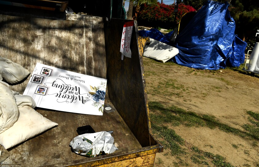 A wedding sign sits in a trash bin ready to be hauled away.