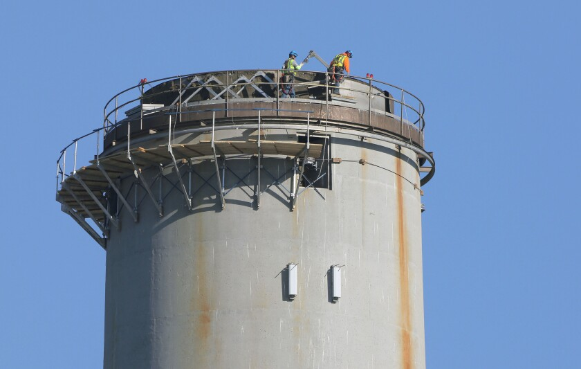 Workers on top of the Encina power plant smokestack prepare it for demolition.