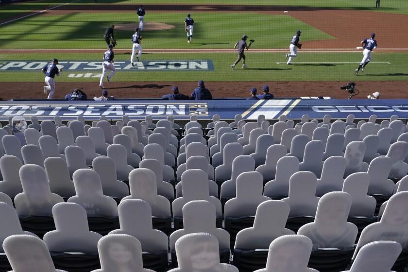 Ante siluetas de fanáticos, recortadas y colocadas en el graderío del Petco Park de San Diego, los Rays de Tampa Bay entran en el terreno para disputar el sexto juego de la Serie de Campeonato de la Liga Americana ante los Astros de Houston, el viernes 16 de octubre de 2020 (AP Foto/Gregory Bull)