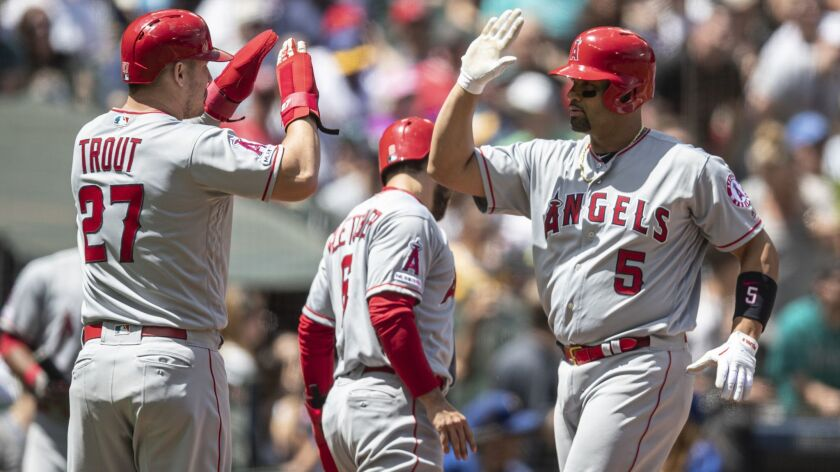 Los Angeles Angels' Albert Pujols, right, is congratulated by teammate Mike Trout after hitting a th