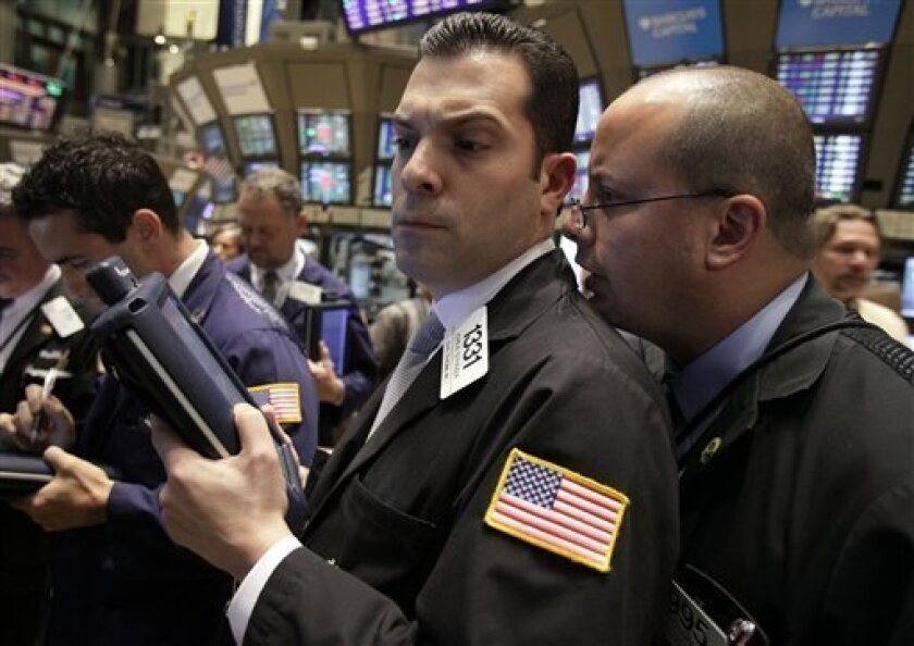 A fellow trader whispers in the ear of John Strazza, left, near the close of trading on the floor of the New York Stock Exchange, Thursday, Sept. 30, 2010, in New York. Stocks are ending a monthlong rally on a weak note, but still chalked up the best September in 71 years. (AP Photo/Richard Drew)