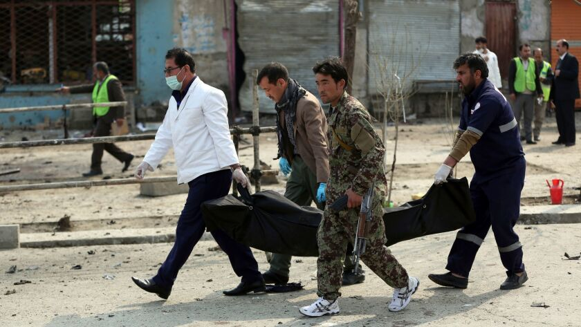 Security personnel carry a body at the site of a suicide attack in Kabul, Friday, March 9, 2018. A s