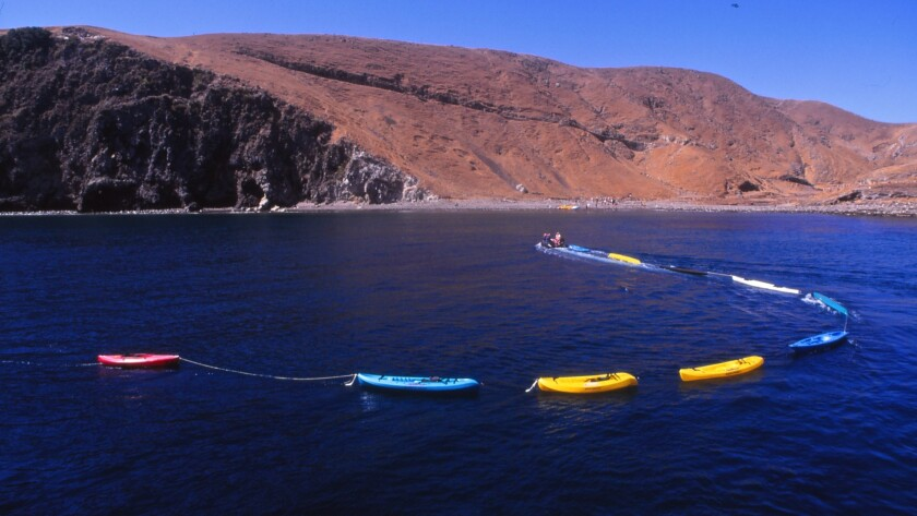 A string of kayaks approaches Scorpion Anchorage on Santa Cruz Island, busiest of the islands in Channel Islands National Park.