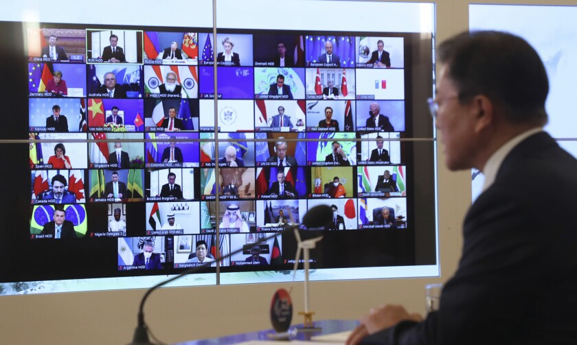 South Korean President Moon Jae-in, right, speaks as the screen showing world leaders at the virtual Leaders Summit on Climate, at the presidential Blue House in Seoul, South Korea, Thursday, April 22, 2021. (Lee Jin-wook/Yonhap via AP)