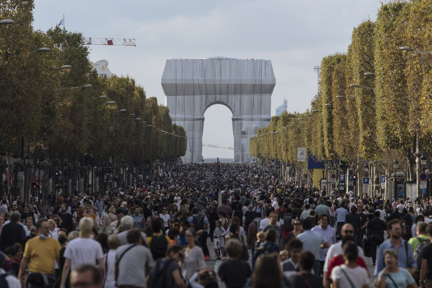 """People walk along the Champs Elysees Avenue, Paris, during the """"day without cars"""", with the Arc de Triomphe in the background, Sunday, Sept. 19, 2021. It is the sixth year the city has held a car free day in an attempt to reduce traffic and ease air pollution. (AP Photo/Lewis Joly)"""