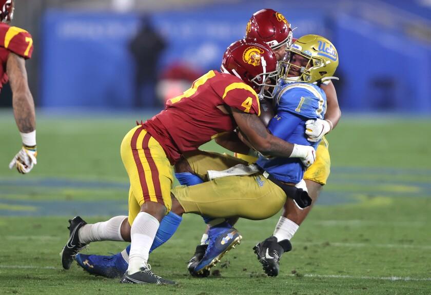 USC defensive back Max Williams (4) helps bring down UCLA quarterback Dorian Thompson-Robinson.