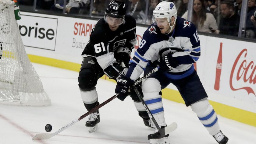 Winnipeg Jets center Bryan Little, right, vies for the puck against Los Angeles Kings defenseman Sea