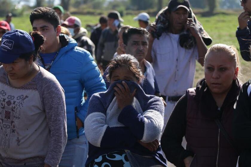 Familiares a la espera de información en la zona donde expertos forenses trabajan este sábado tras la explosión de una toma clandestina de gasolina de Petróleos Mexicanos (Pemex), en Tlahuililpan, Hidalgo (México). EFE