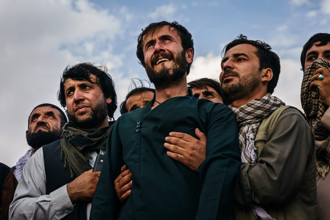 Ramal Ahmadi, center, is supported by family members as he weeps.
