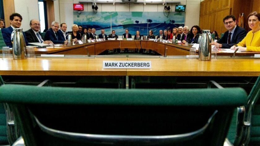 """A Nov. 27, 2018, photo made available by the House of Commons shows the International Grand Committee with representation from nine countries and an empty chair for Facebook CEO Mark Zuckerberg. Lawmakers grilled a Facebook exec, Richard Allan, on disinformation and """"fake news."""""""