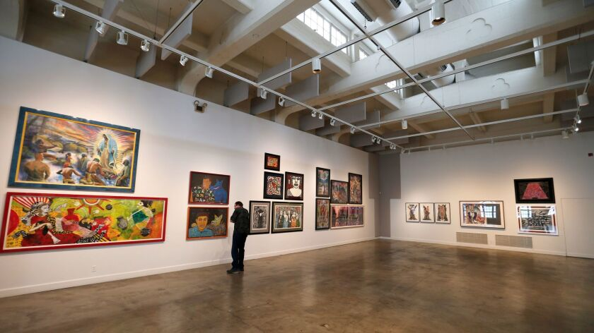 A visitor to the Riverside Art Museum looks at works from the collection of actor Cheech Marin, know