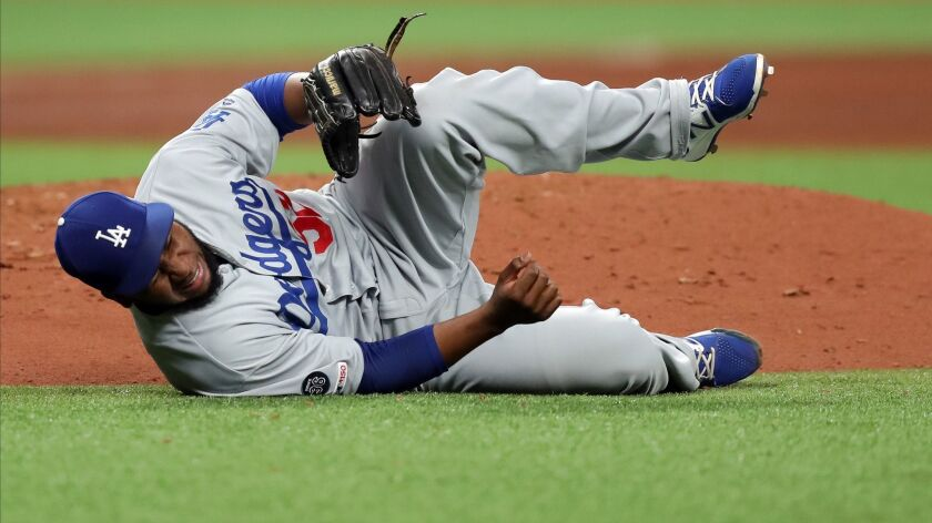 Los Angeles Dodgers reliever Pedro Baez reacts after he was hit by a line drive in the seventh inning May 21. X-rays on his right knee were negative, and Baez, walking with a limp after the game, said the knee felt significantly better.