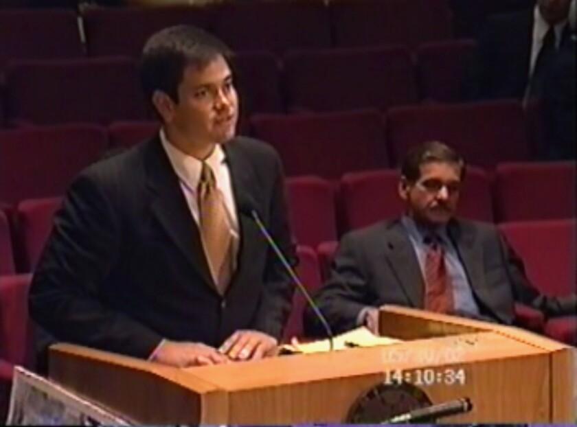 Marco Rubio, a la izquierda, en una reunión del condado Miami-Dade, expresando su apoyo a un proyecto de construcción promovido por Carlos C. Lopez-Cantera, sentado a la derecha. Foto tomada del video de la reunión el 30 de mayo del 2002. (Miami-Dade Board of County Commissioners via AP)