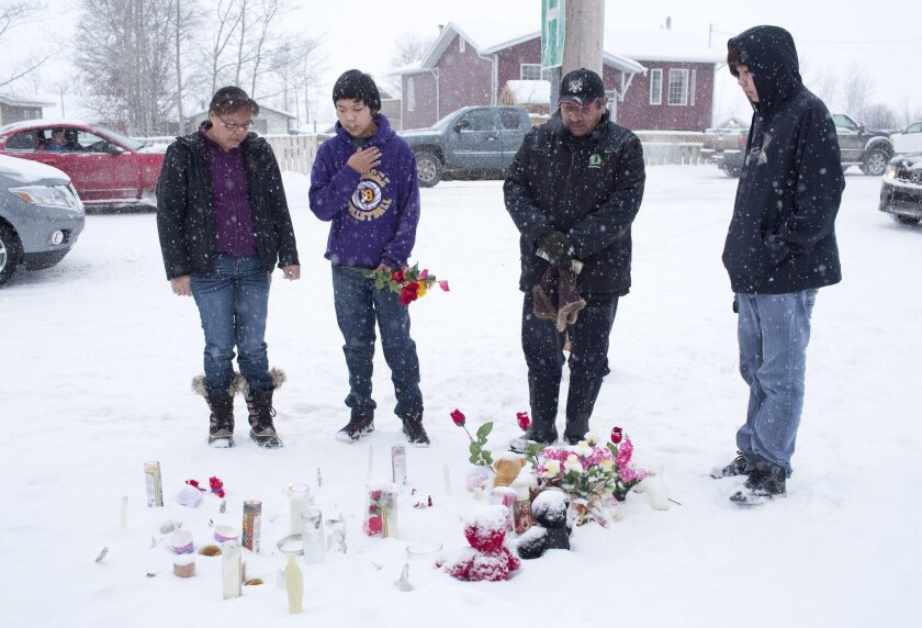 A family in La Loche, Saskatchewan, pay their respects Saturday to victims of the school shooting.