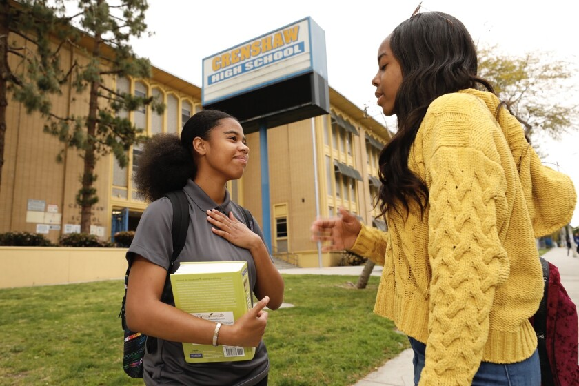 Kaya Buckley, left, and Kaelyn Campbell, both seniors at Crenshaw High School, talk before heading to class Thursday morning. The campus is just blocks from where rapper Nipsey Hussle was shot and killed.