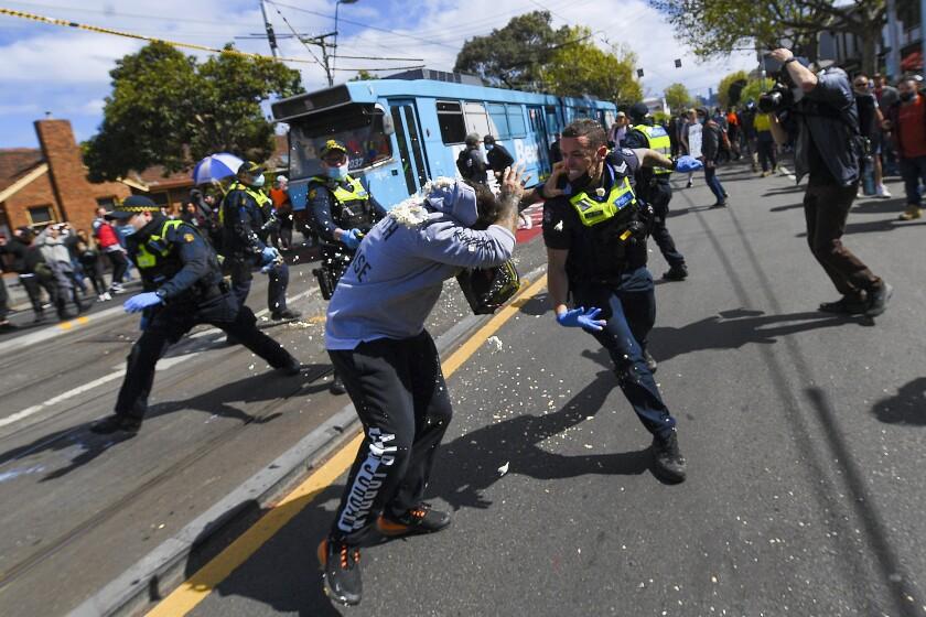 Policías se enfrentan a manifestantes que protestaron violentamente contra las restricciones del coronavirus, en Melbourne, Australia, el 18 de septiembre de 2021. (James Ross/AAP Image via AP)