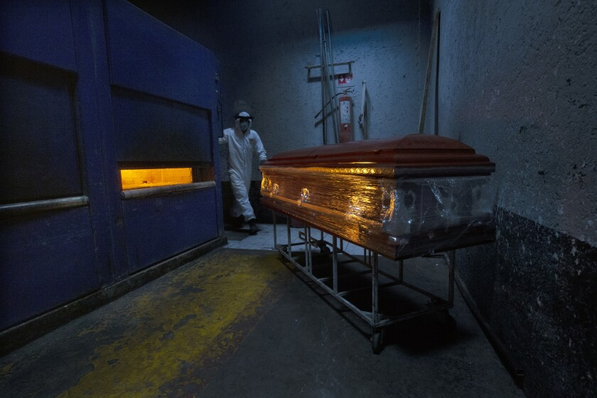 A crematorium worker prepares an oven for a COVID-19 victim at the Panteón de San Nicolás Tolentino cemetery in the Iztapalapa neighborhood of Mexico City, Thursday, June 4, 2020. Gravediggers and crematorium workers in Mexico are struggling to keep pace as the country registers escalating coronavirus death numbers while gradually easing some restrictions aimed at curbing COVID-19. (AP Photo/Marco Ugarte)