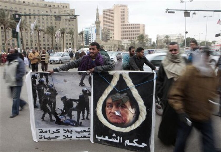 "An Egyptian holds posters at Tahrir Square, the focal point of the Egyptian uprising, in Cairo, Egypt, Friday, March 2, 2012, depicting Egypt's ousted President Hosni Mubarak that reads, in Arabic, ""The people's verdict"", and another showing soldiers beating a female protestor in Cairo which reads: ""A nation without dignity is a nation without life"". (AP Photo/Amr Nabil)"