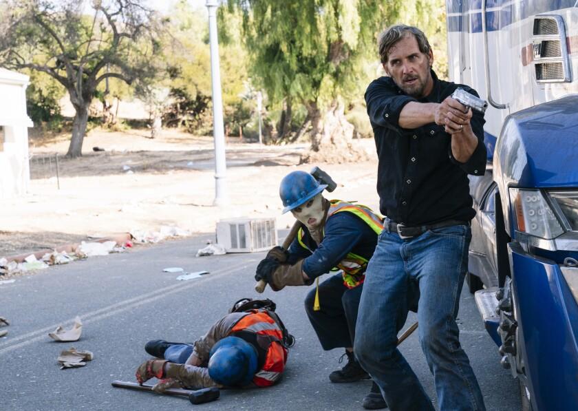 A man points a gun as a masked man squats behind him holding a sledgehammer.
