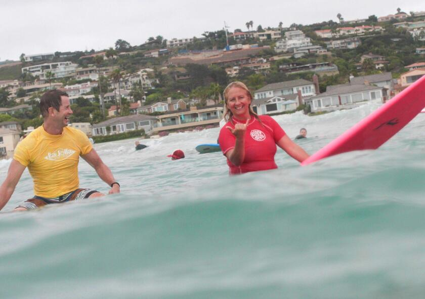 Surf Diva's Izzy Tihanyi (right) gives a surf lesson in La Jolla Shores.