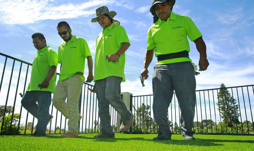 Workers from the Mission Valley-based company OmegaTurf walked on artificial grass to stretch it out as it was being installed at a home in La Jolla on March 17. / photo by K.C. Alfred * U-T San Diego