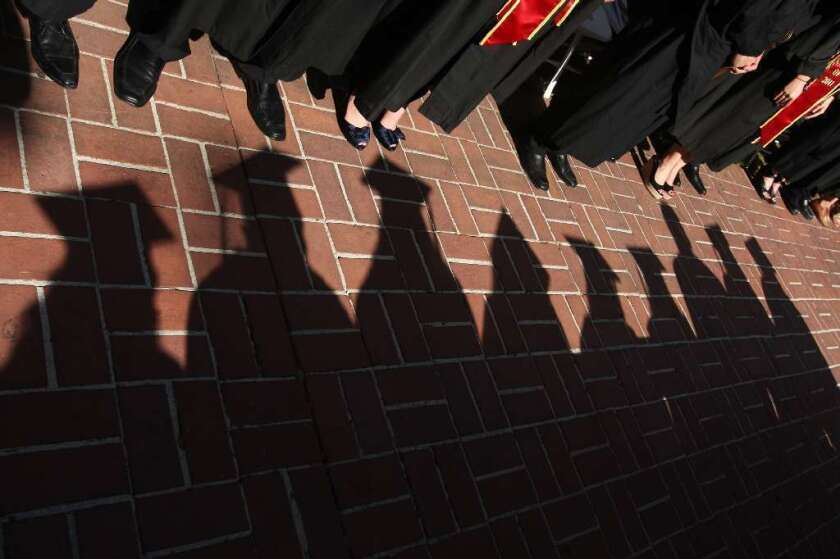 Shadows of students in caps and gowns on paving bricks near other people in black graduation gowns.