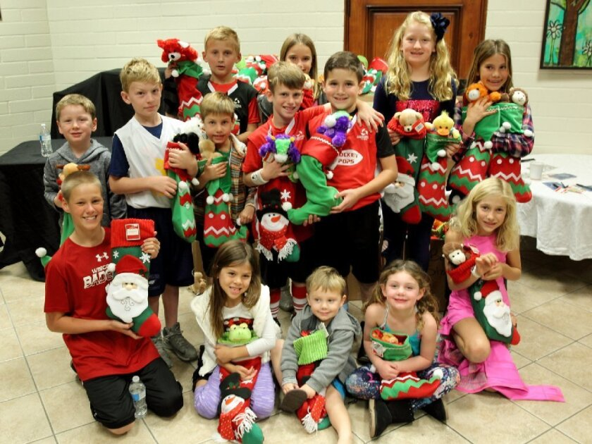 The Kidz Kare participants from the RSF Community Center show the stockings they stuffed for the San Pasqual Academy foster teens.