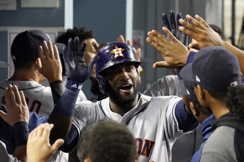 El jugador de los Astros de Houston Yordan Álvarez es felicitado por su jonrón de dos carreras en el dugout, en el octavo inning de su juego de béisbol contra los Dodgers de Los Ángeles, el martes 3 de agosto de 2021 en Los Ángeles. (AP Foto/Marcio Jose Sanchez)