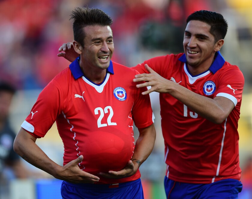 Roberto Gutierrez of Chile celebrates with teammate Diego Valdez, right, after scoring a goal against the U.S. national team during a friendly match at El Teniente Stadium in Rancagua, Chile.
