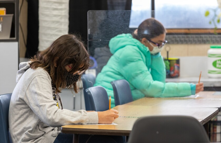 McAuliffe Elementary fifth-graders Mercedes Hopkins and Maia Ramirez are separated by plexiglass during class