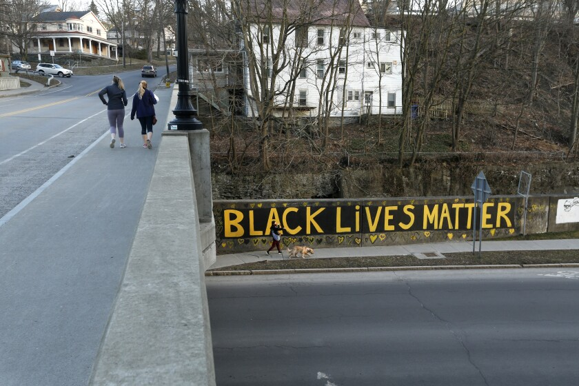 Black Lives Matter is seen along East Green Street where is passes under South Aurora Street, Monday, March 22, 2021, in Ithaca, N.Y. The nationwide reexamination of policing after the killing of George Floyd has led the Ivy League town in New York to consider an ambitious and contentious plan to remake its force. A proposal would replace the 63-officer Ithaca Police Department with a new Department of Community Solutions and Public Safety. (AP Photo/John Munson)