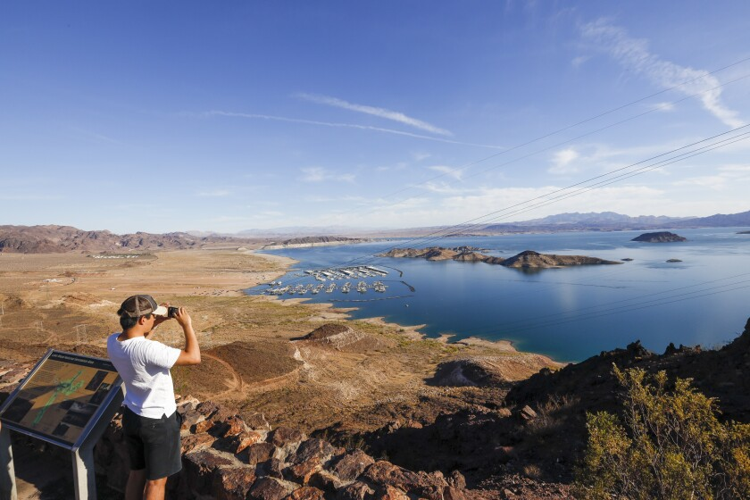 A tourist at a Lake Mead overlook snaps a photo.