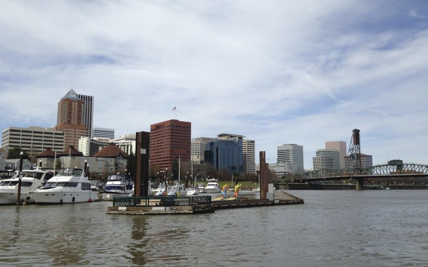 This March 18, 2016 photo shows the Willamette River and skyline in the background in Portland, Ore. Fiercely protective of its reputation as one of the most eco-friendly cities in the country, Portland is reeling from the discovery of poisonous heavy metals in the air and the ground of neighborhoods where thousands of people live, work and attend school. (AP Photo/Terrence Petty)