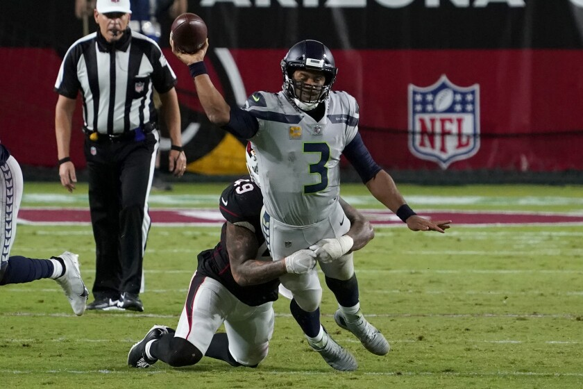 Seattle Seahawks quarterback Russell Wilson (3) gets the throw off as Arizona Cardinals linebacker Kylie Fitts makes the hit during the second half of an NFL football game, Sunday, Oct. 25, 2020, in Glendale, Ariz. (AP Photo/Rick Scuteri)