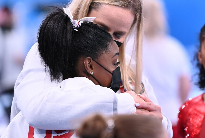 U.S. gymnast Simone Biles is consoled after withdrawing from the women's team competition.