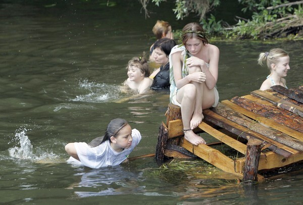 """People take a bath in a river during a hot day at the """"Pustiye Holmi"""" (Empty Hills) open-air non-format art and music festival outside the village of Gorokhovka, 154 miles south of Moscow, June 11, 2011. Thousands of people spent four nights in the open air to enjoy alternative arts and music."""