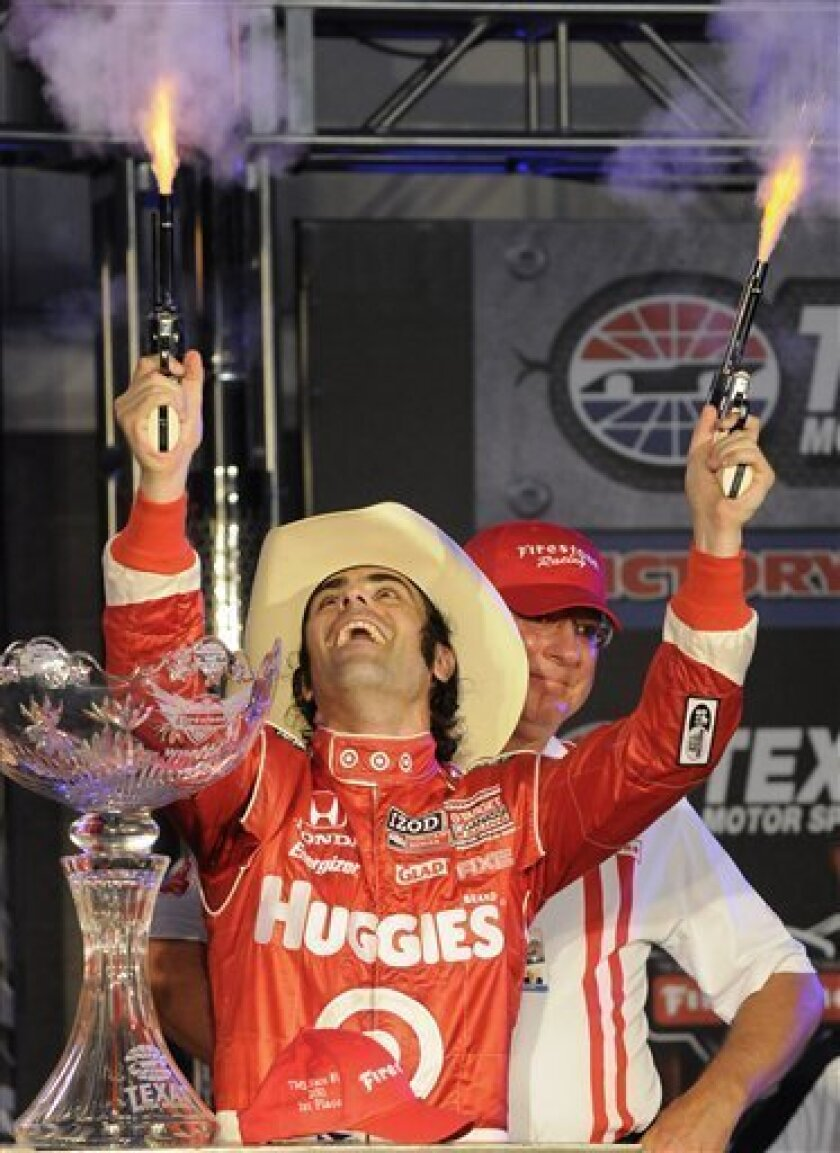 IndyCar driver Dario Franchitti shoots pistols after wining the first auto race of the Texas Firestone Twin 275s at Texas Motor Speedway in Fort Worth, Texas, Saturday, June 11, 2011. (AP Photo/Ralph Lauer)