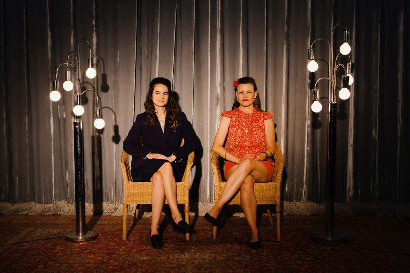 Two women sit in chairs between lights and in front of a curtain.
