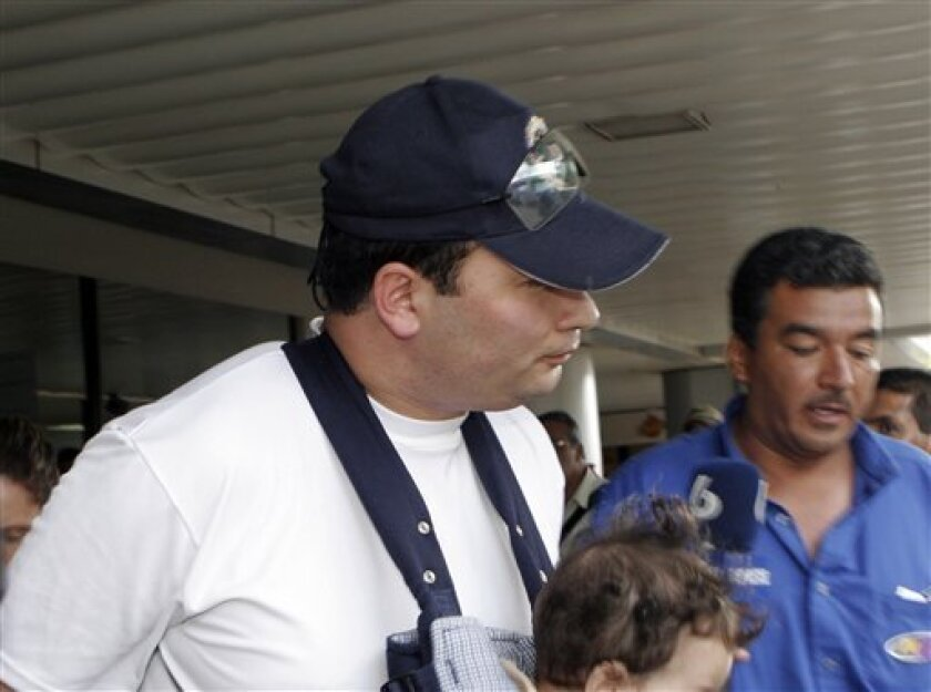 FILE - In this March 4, 2007 file photo Guatemala's former sub-director of the National Civil Police Javier Figueroa arrives with his family at International Airport Juan Santamaria in Alajuaela, Costa Rica. Austrian prosecutors have charged the former senior Guatemalan police official with murder in connection with the shooting deaths of seven prison inmates in his homeland, as it was announced Monday, May 13, 2013. (AP Photo/Kent Gilbert, File) EFE OUT