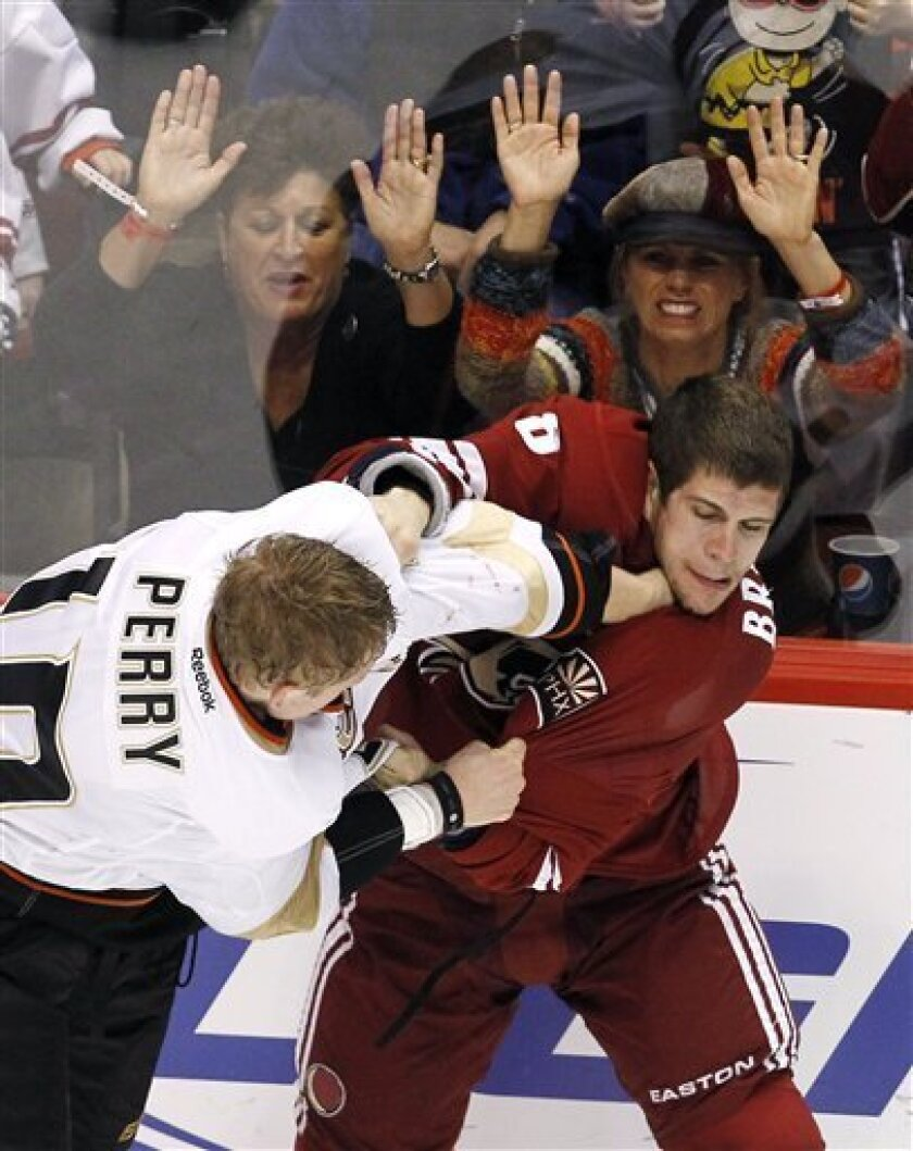 Phoenix Coyotes' Gilbert Brule, right, fights with Anaheim Ducks' Corey Perry as fans pound on the glass during the second period in an NHL hockey game, Saturday, March 31, 2012, in Glendale, Ariz. (AP Photo/Ross D. Franklin)