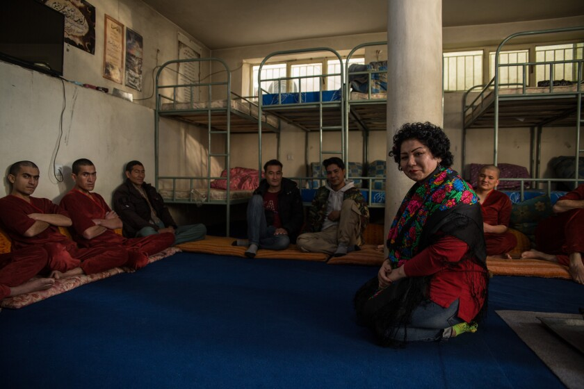 Laila Haidri sits with men at her drug shelter, Mother Camp