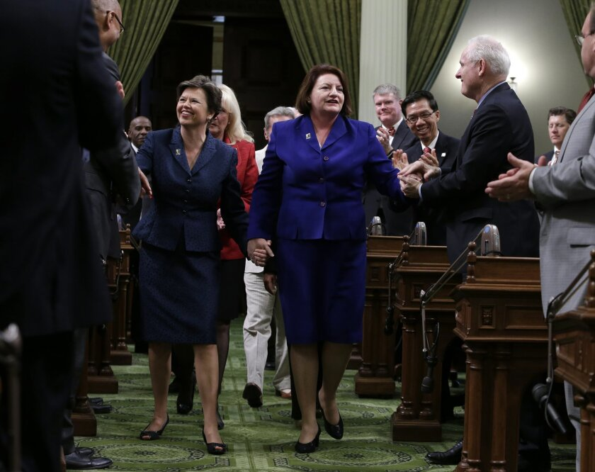 FILE - In this Monday, May 12, 2014 file photo, Assembly Speaker-elect Toni Atkins, D-San Diego, right, walks hand in hand with her spouse, Jennifer LeSar, to the rostrum of the Assembly where she took the oath of office as the 69th Assembly Speaker at the Capitol in Sacramento, Calif.   Atkins tol