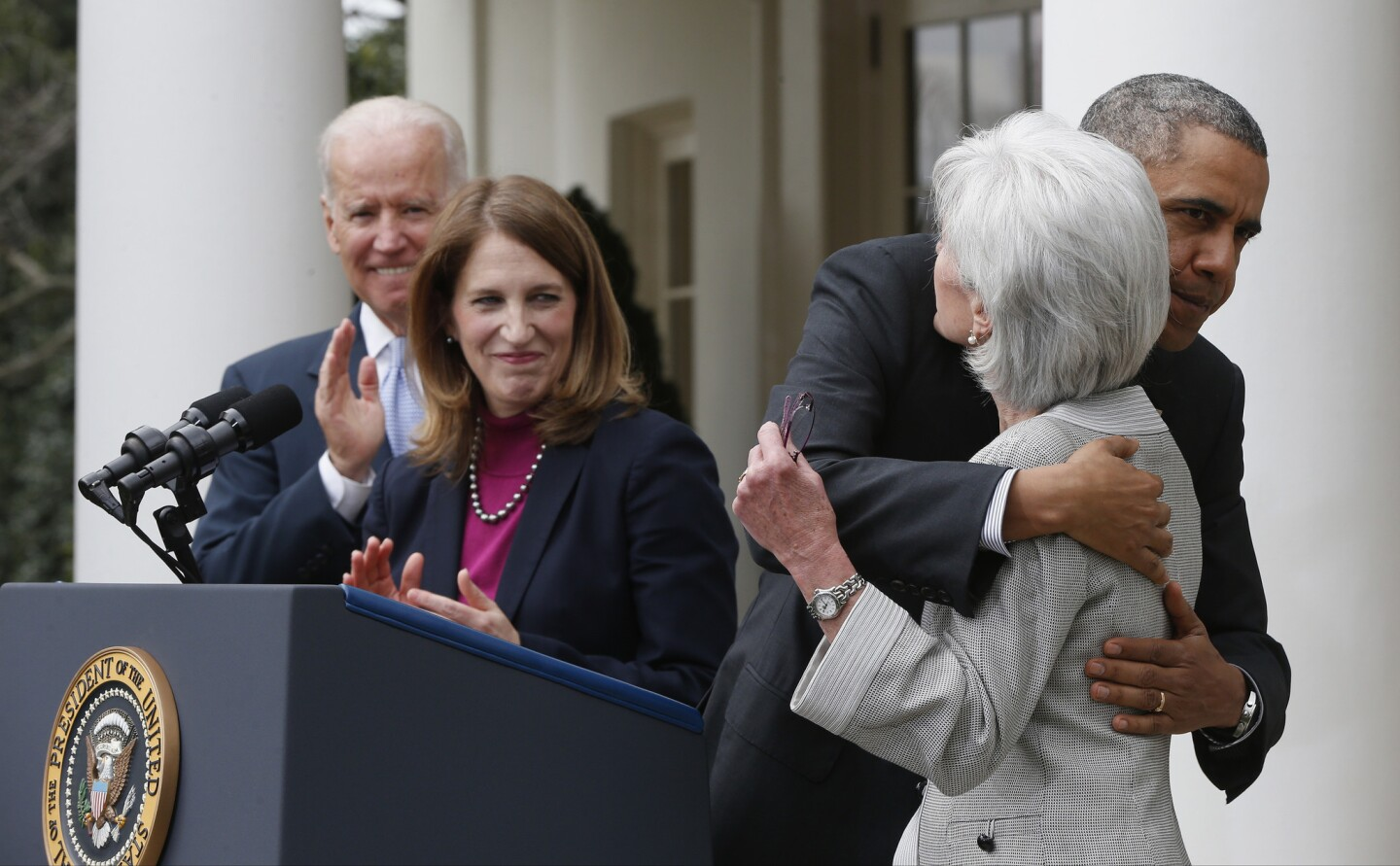 President Obama hugs outgoing Health and Human Services Secretary Kathleen Sebelius as he stands with Vice President Joe Biden and Sylvia Mathews Burwell, his nominee to replace her.