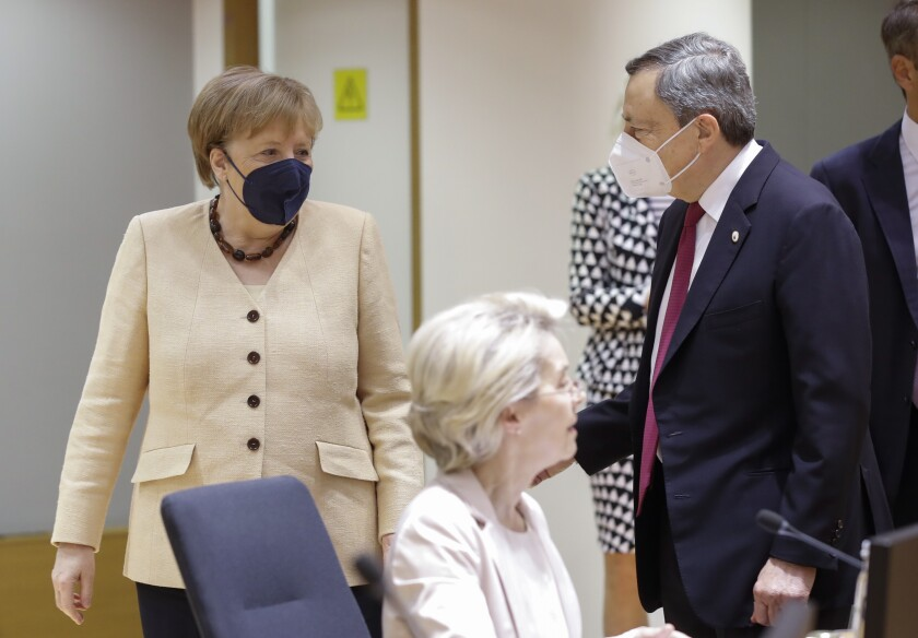German Chancellor Angela Merkel, left, talks to Italian Prime Minister Mario Draghi during an EU summit at the European Council building in Brussels, Friday, June 25, 2021. During the second of two days summit EU leaders are discussing the economic challenges the bloc faces due to coronavirus restrictions and will review progress on their banking union and capital markets union. (Olivier Hoslet, Pool Photo via AP)