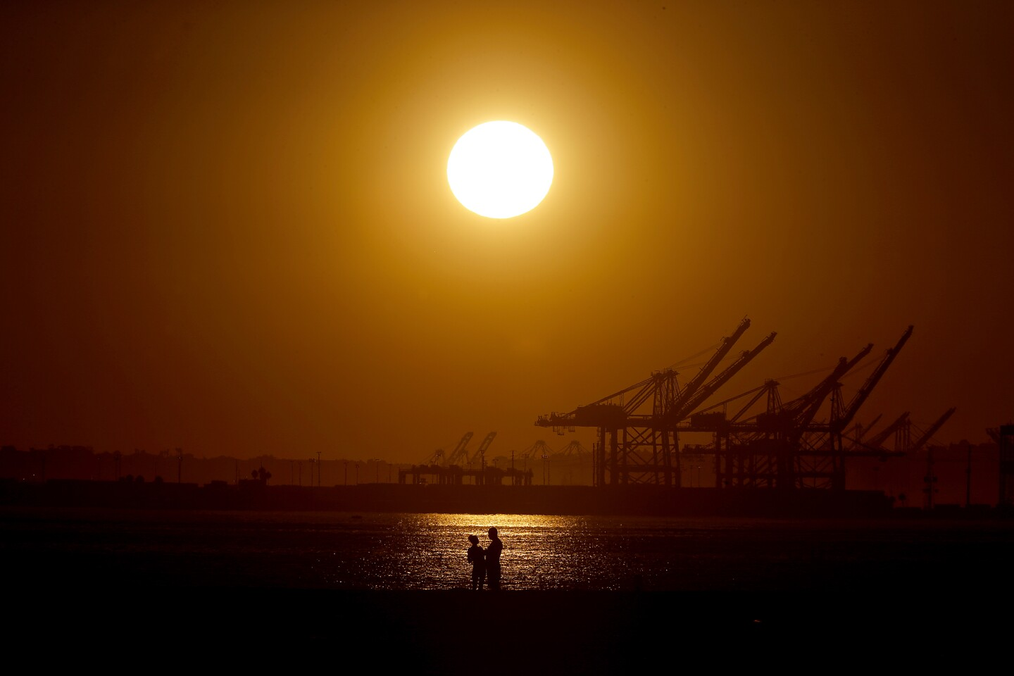 LONGE BEACH, CALIF. - OCT. 22, 2019. A couple take in the sunset at Belmont Shore in Long Beach, parts of which hit 98 degrees on Tuesday, Oct. 22, 2019. (Luis Sinco/Los Angeles Times)